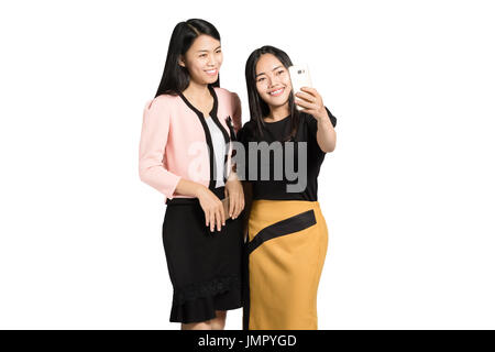 portrait of two beautiful asian business woman smiling and making a selfie with smart phone. Isolated on white background - Stock Photo