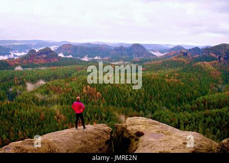 Runner in pink jacket and light black trousers. Short ginger man in his target. Tired sportsman take a rest on thepath in  rocky mountains.
