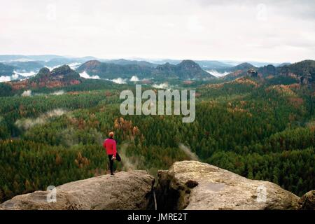 Runner makes stretching with leg. Short ginger main pink jacket and light black trousers. Tired sportsman take a rest on thepath in  rocky mountains.