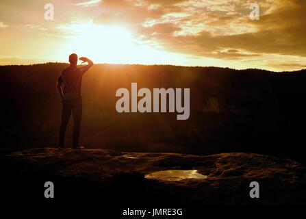Runner on the peak. Man in his target with hand in the air. Hiker in black running trousers and shinning blue sweaty - Stock Photo