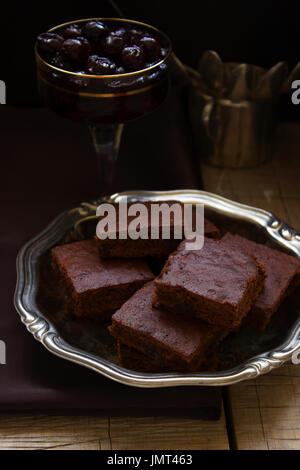 Chocolate brownies and cherry jam on a wooden table - Stock Photo