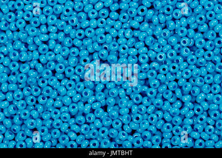Multicolored blue glass seed beads background.