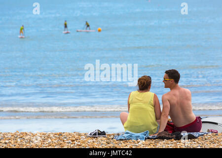 Couple sitting on the beach at Lyme Regis with paddleboarders in the distance, Lyme Regis, Dorset in July - Stock Photo