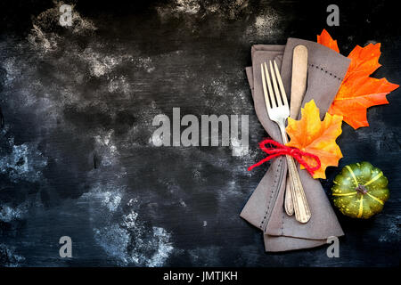 Autumn menu concept - rustic table place setting with a fork and a knife wrapped in a napkin with fall season decorative leaves and pumpkins with copy