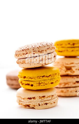 some stacks of appetizing macarons with different colors and flavors on a white background - Stock Photo