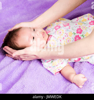 Portrait of a little adorable infant baby girl lying on the tummy on the pillow with mother hand stroking her head - Stock Photo