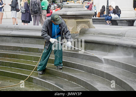 A new York City Parks Department worker power washing the area around the fountain in Washington Square Park in - Stock Photo