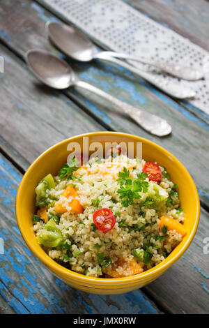 Tabbouleh salad on a rustic table - Stock Photo