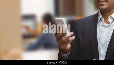 Digital composite of Business man looking at a phone against office background - Stock Photo