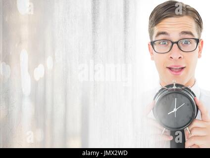 Digital composite of man holding clock in front of bright light - Stock Photo
