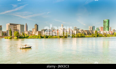 panoramic view of frankfurt skyline, pleasure boat in foreground,as seen from the south bank of river main, frankfurt - Stock Photo