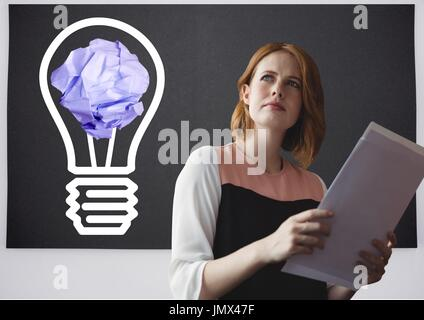 Digital composite of Woman holding tablet standing next to light bulb with crumpled paper ball in front of blackboard - Stock Photo