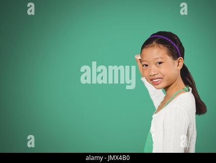 Digital composite of Girl writing in front of green blank background - Stock Photo