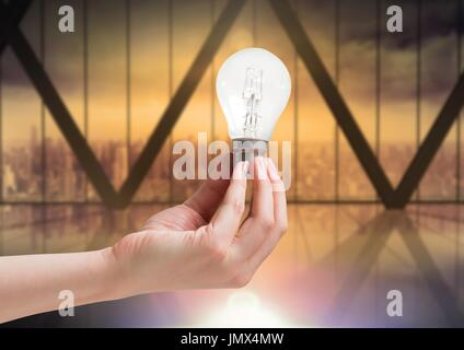Digital composite of Hand holding light bulb by windows - Stock Photo