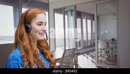 Digital composite of Happy customer care representative woman against office background - Stock Photo