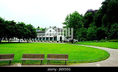 Wooden benches in a park with background of Baden-Baden Casino, Baden-Baden, Baden-Württemberg , Germany - Stock Photo