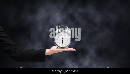 Digital composite of Arm holding clock in front of dark background - Stock Photo