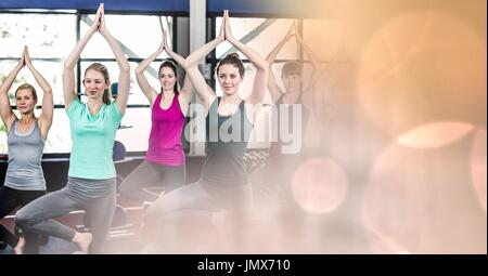 Digital composite of Women doing yoga and peach bokeh transition - Stock Photo