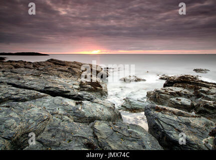The rugged rocks along the north coast of Anglesey, Wales, near Cemlyn, are the basis for this sunset shot, looking - Stock Photo