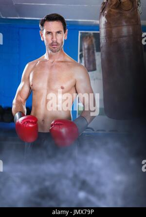 Digital composite of Boxer fighter man with transition and punch bag - Stock Photo