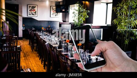 Digital composite of Hand photographing through smart phone in restaurant - Stock Photo