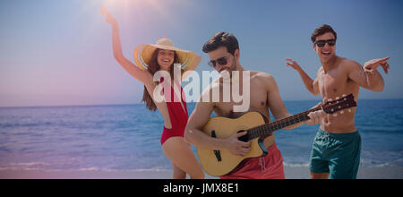 Friends playing music in swimwear against beach against clear sky - Stock Photo