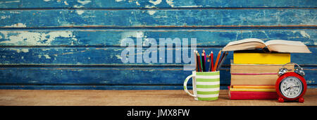 Stacked books with alarm clock and colored pencils on wooden table - Stock Photo