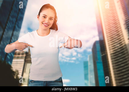 Portrait of smiling brunette woman in front of white background against city - Stock Photo