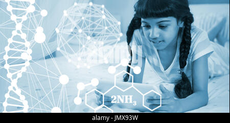 Composite image of molecular structure against girl using tablet while lying on bed at home - Stock Photo