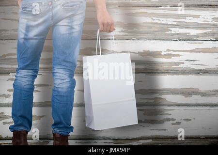 Mid section of man carrying bag against wood plank with grey paint - Stock Photo
