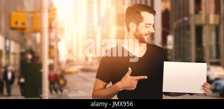 Smiling young man pointing towards blank cardboard against picture of a city - Stock Photo