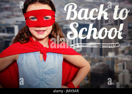 Little girl pretending to be a superhero  against towers and building in city - Stock Photo