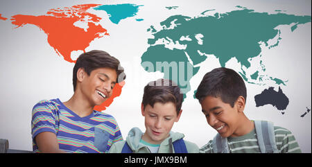 Boy with friends using digital tablet on bench against grey background - Stock Photo