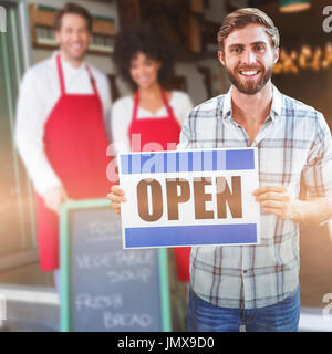 Portrait of male owner holding open sign against smiling colleagues posing behind a chalkboard - Stock Photo