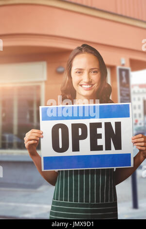 Portrait of female owner with open sign against cafe building exterior on street - Stock Photo