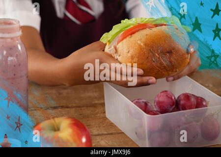 Digital composite image of stars against schoolgirl having sandwich - Stock Photo
