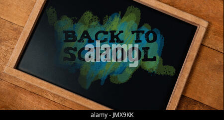 Back to school text on green and blue splash against tilt chalkboard on wooden table - Stock Photo