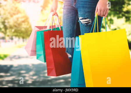 Women holding bag with blank space against blur view of park - Stock Photo