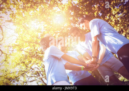 Volunteers forming a hand stack in the park - Stock Photo