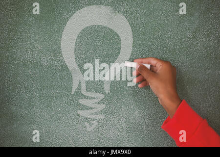 Digital composite image of yellow light bulb against hand writing on chalk board - Stock Photo