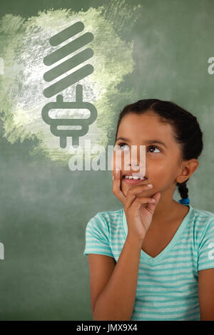 Digital composite image of light bulb on green spray paint against thoughtful young girl - Stock Photo