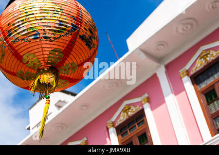 Red Chinese lantern against blue sky & pink facade of Sino-Portuguese townhouse in Soi Romanee, Phuket Old Town, - Stock Photo