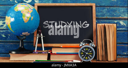Studying text on white background against empty blackboard with school supplies - Stock Photo
