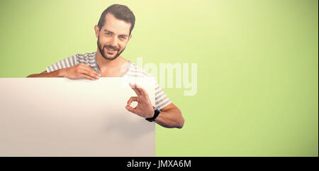 Portrait of man showing ok sign while holding blank cardboard against green background - Stock Photo