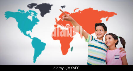 Boy with sister pointing against grey background - Stock Photo
