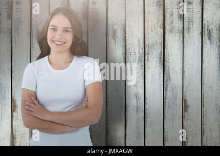 Portrait of confident model standing with arms crossed against wood background - Stock Photo