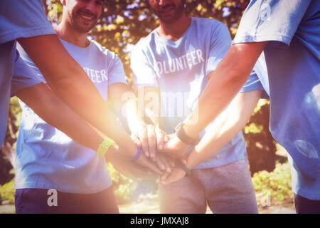 Volunteers forming hands stack while standing at park - Stock Photo