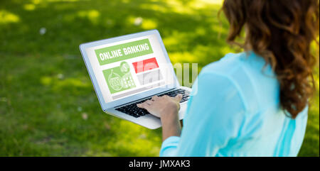 Online banking text on gray display against woman using laptop in park - Stock Photo