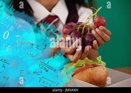 Digital composite image of algebraic formulas against schoolgirl having grape fruit - Stock Photo