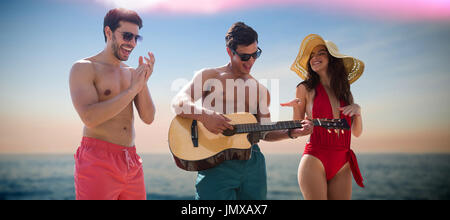 Friends playing music in swimwear against idyllic view of sea - Stock Photo